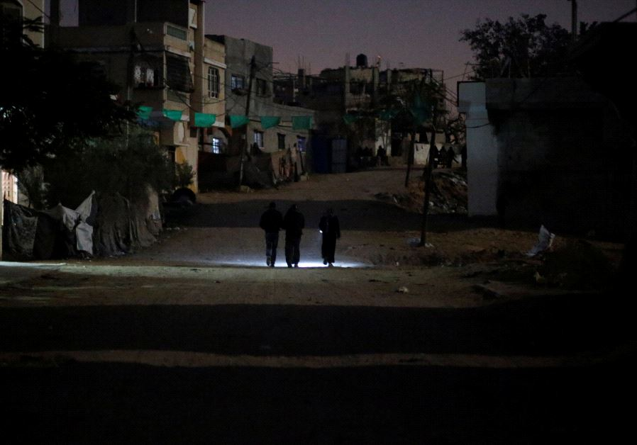 Palestinians walk on a road during a power cut in Beit Lahiya in the northern Gaza Strip. (Reuters)