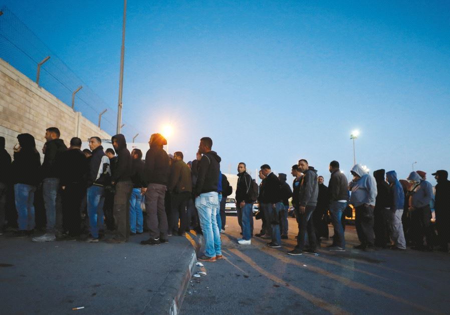 Palestinians working in Israel stand in line early in the morning as they wait to cross through Kalandiya checkpoint near Ramallah in April. Credit: Reuters