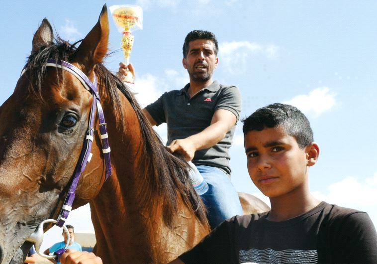 Azam's owner rides the horse and holds up their winning trophy.