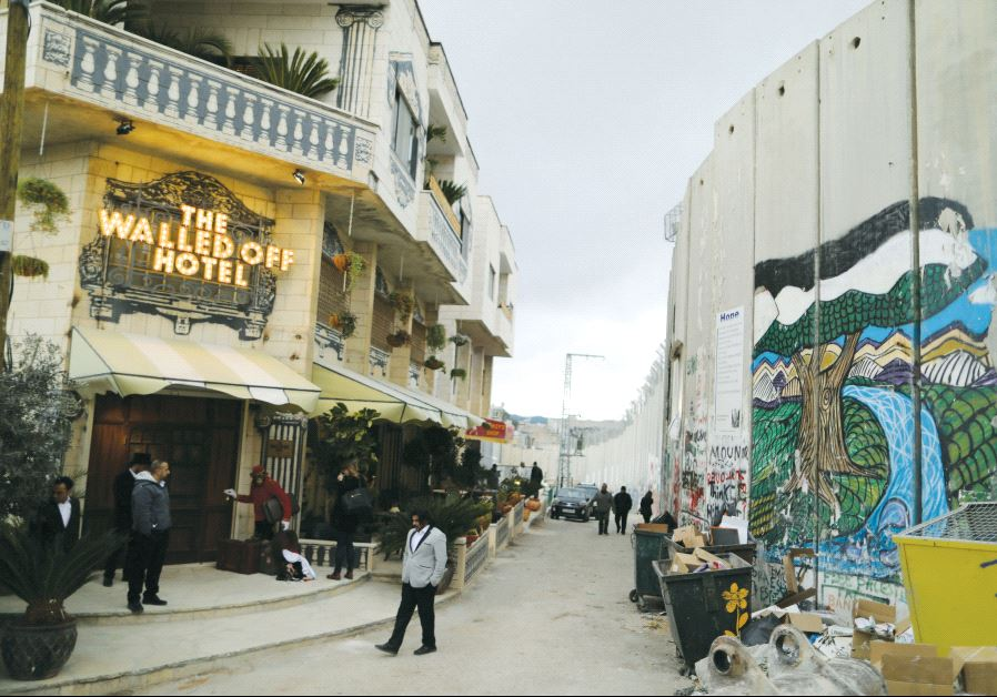People stand outside the Walled Off Hotel, which was opened by street artist Banksy, in Bethlehem (photo credit: REUTERS)