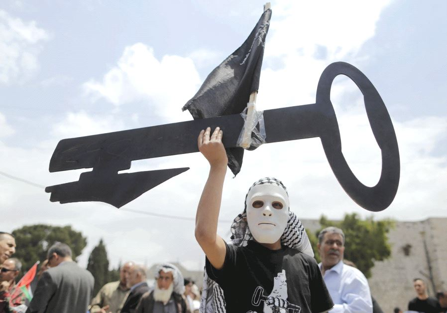 A Palestinian wearing a mask holds a cut-out of a key during a rally ahead of the 'Nakba Day' in Bethlehem in 2015 (photo credit: REUTERS)