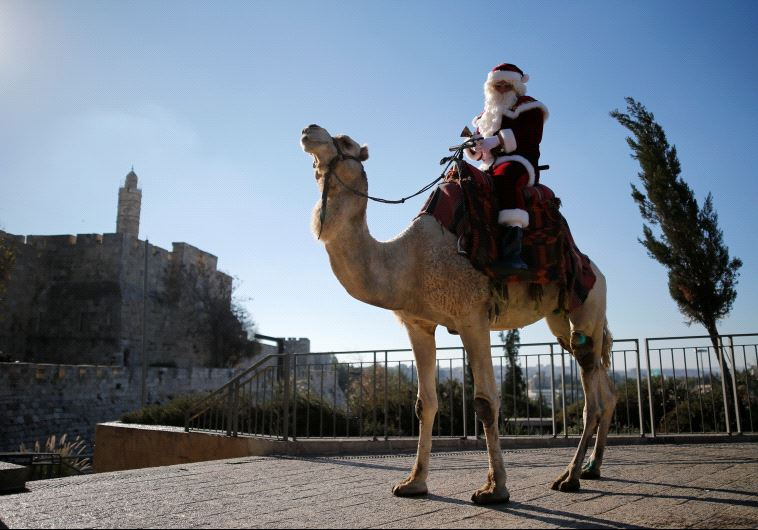 Israeli-Arab Issa Kassissieh wears a Santa Claus costume as he rides a camel during an annual Christmas tree distribution by the Jerusalem municipality, December 20, 2016. (Reuters)