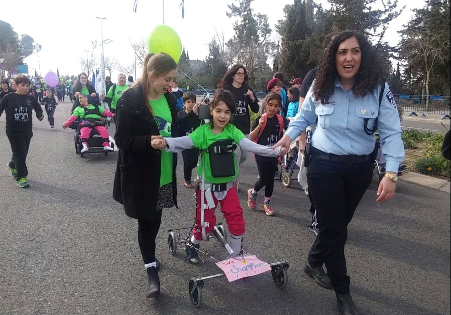 Volunteers help children with disabilities participate in the Jerusalem Marathon. (photo credit: COURTESY OF ALEH)