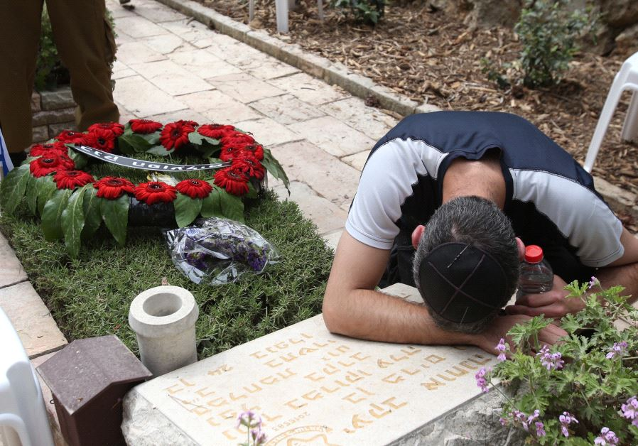 A man mourns over a gravestone at the national military cemetery on Mount Herzl in Jerusalem on Memorial Day, May 1, 2017 (MARC ISRAEL SELLEM)