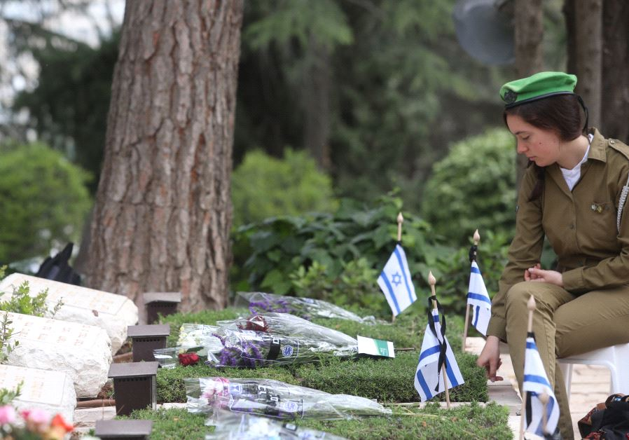 An IDF soldier seats next to a gravestone at the national military cemetery on Mount Herzl in Jerusalem on Memorial Day, May 1, 2017 (MARC ISRAEL SELLEM)‏