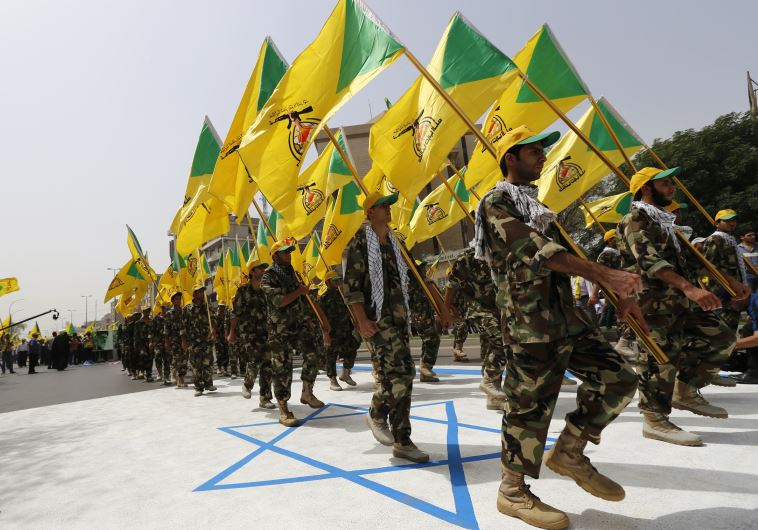 Iraqi Shi'ite Muslim men from the Iranian-backed group Kataib Hezbollah wave the party's flags as they walk along a street painted in the colours of the Israeli flag during a parade marking the annual Quds Day (Reuters)