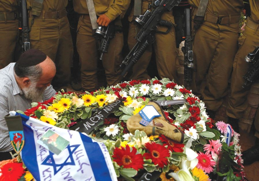 SOLDIERS STAND next to the grave of their comrade Lieutenant Hadar Goldin during his funeral in Kfar Saba in August 2014 (Reuters)