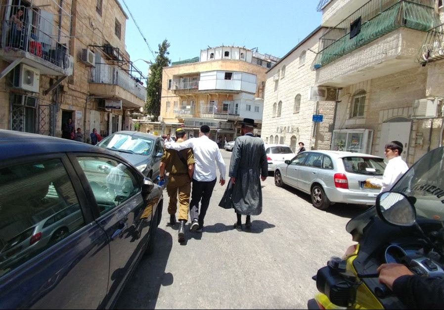 A soldier is escorted away from an anti-Zionist mob in the capital's Mea She'arim neighborhood, June 9 2017 (HAREDI EXTREMISTS PROTESTS GROUP)