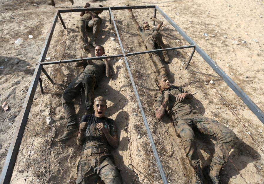 Young Palestinians crawl under an obstacle during a military-style exercise at a Hamas summer camp in Rafah in the southern Gaza Strip July 27, 2017. (Reuters)