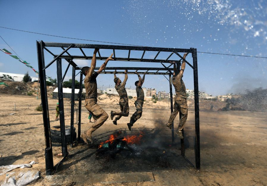 Young Palestinians swing across monkey bars over fire during a military-style exercise at a Hamas summer camp in Rafah in the southern Gaza Strip July 27, 2017. (Reuters)