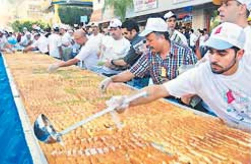 Bakers prepare a giant kunafa in Nablus. The local (photo credit: AP)