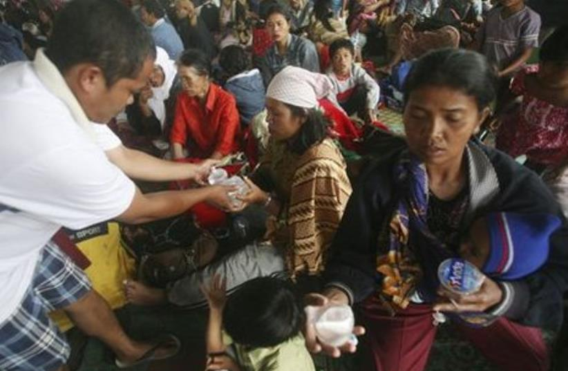 Indonesian villagers who fled the area surrounding the erupting volcano receiving aid.