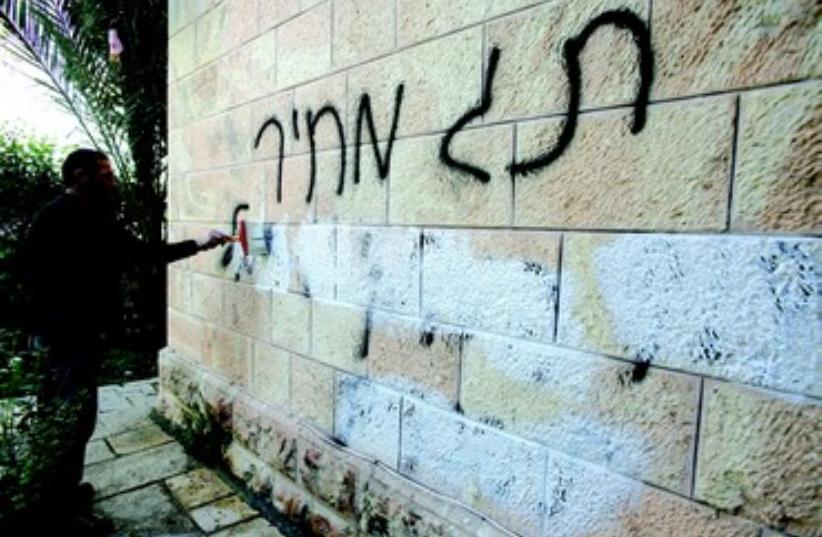 Graffitis de Tag Mehir effaces d'un mur d'eglise (photo credit: REUTERS)
