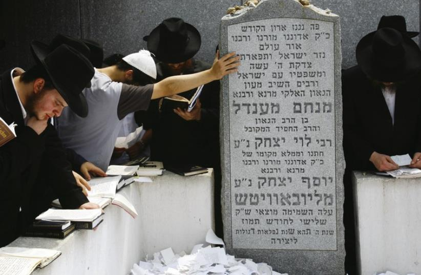 Followers of the late Rabbi Menachem Mendel Schneerson pray at his grave at the Old Montefiore Cemetery in the Queens section of New York city. (photo credit: REUTERS)