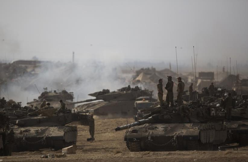 Israeli soldiers stand atop a tank at a staging area, near the border with the Gaza Strip (photo credit: REUTERS)