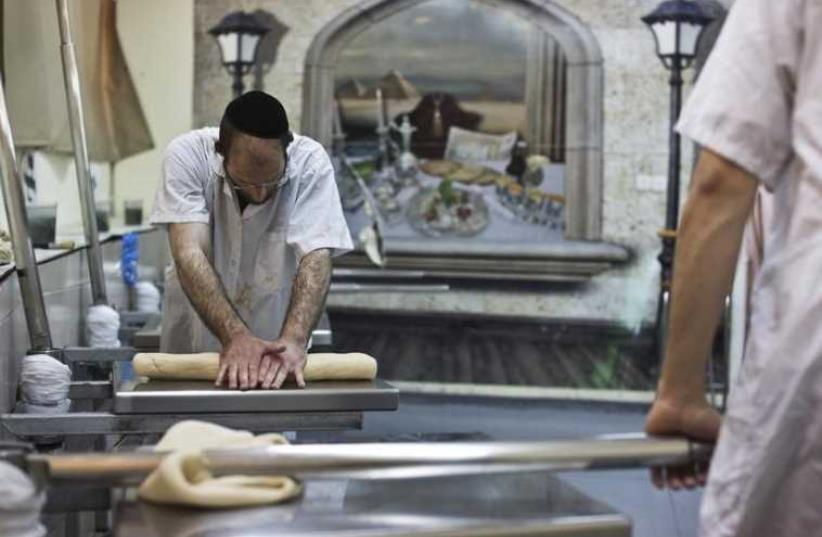 An ultra-Orthodox Jewish man kneads dough as he prepares matza (photo credit: REUTERS)