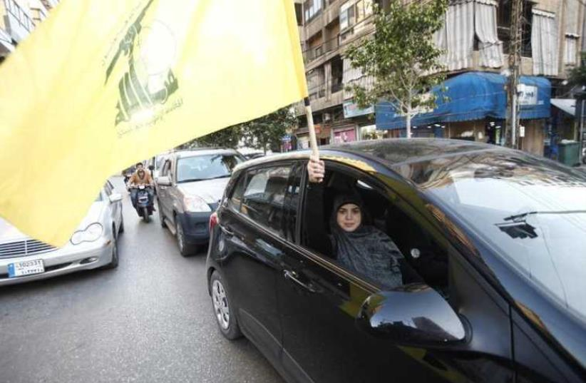 A Hezbollah supporter waves a flag in Beirut's southern suburbs (photo credit: REUTERS)