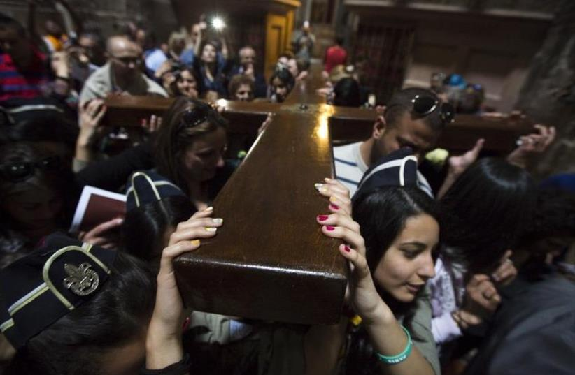 Christians carry a cross after a procession in the Church of the Holy Sepulchre on Good Friday, during Holy Week in Jerusalem's Old City (photo credit: REUTERS)