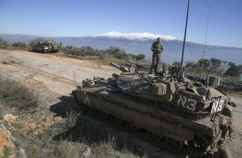An IDF soldier stands atop a tank near the Lebanese border (photo credit: REUTERS)
