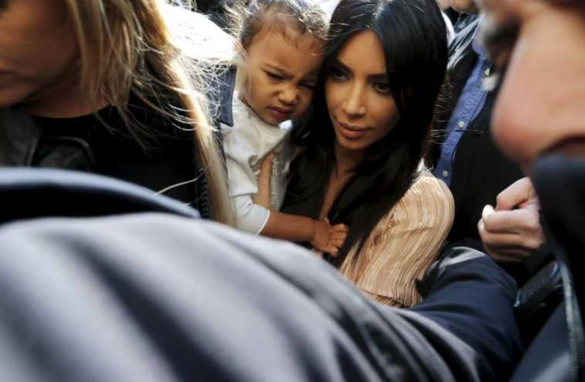 U.S. reality TV star Kim Kardashian (C) holds her toddler daughter North West as they arrive for a baptism ceremony at the Cathedral of Saint James in Jerusalem's Old City April 13, 2015. (photo credit: REUTERS)