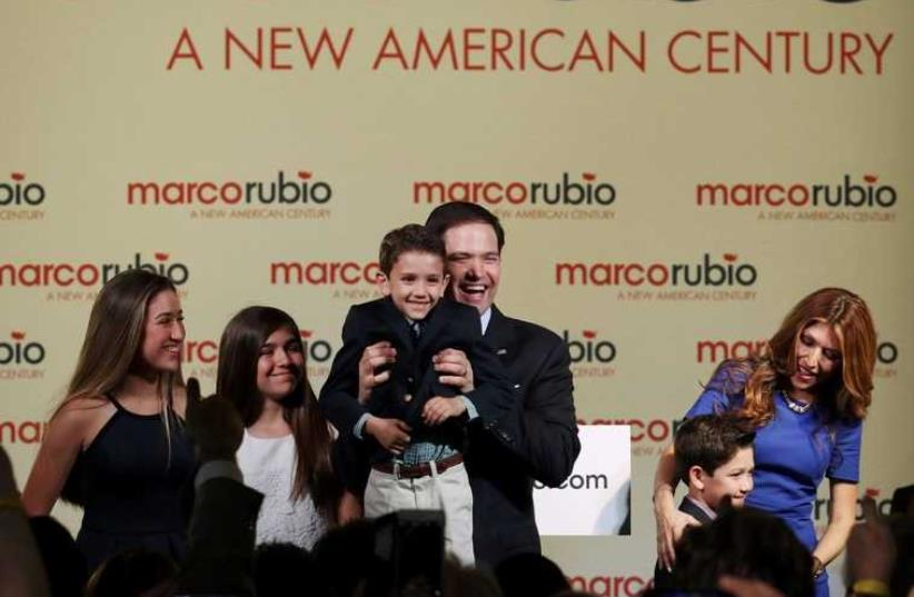 U.S. Senator Marco Rubio (R-FL) holds up his son Anthony as he stands with family members, including his wife Jeanette (R), after he announced his bid for the Republican nomination in the 2016 U.S. presidential election race during a speech at Freedom Tower in Miami, Florida (photo credit: REUTERS)