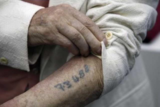 A Holocaust survivor shows his prisoner number tattooed on his arm, Yad Vashem, Jerusalem (photo credit: REUTERS)