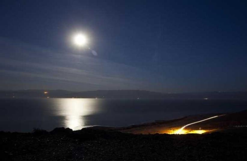 The moon shines in the night sky above the Dead Sea (photo credit: REUTERS)