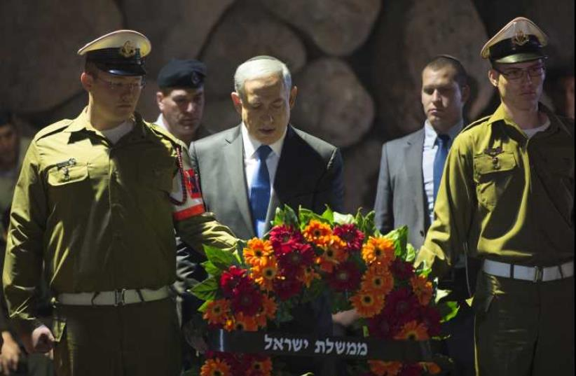 Netanyahu lays wreath during Holocaust Remembrance Day Ceremony at Yad Vashem in Jerusalem (photo credit: AMOS BEN GERSHOM, GPO)