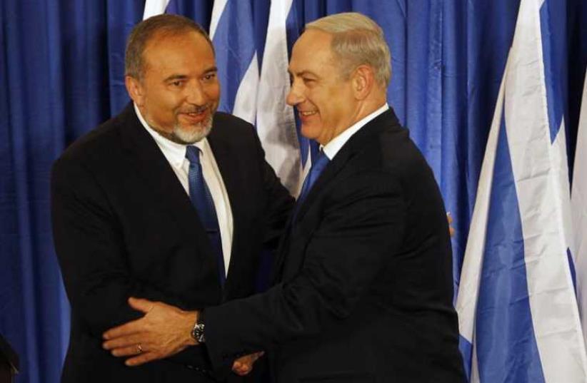 Prime Minister Benjamin Netanyahu (R) shakes hands with Foreign Minister Avigdor Liberman (photo credit: REUTERS)