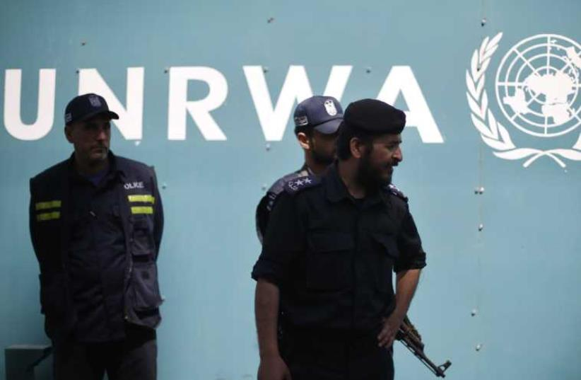 Palestinian policemen loyal to Hamas guard outside the UNRWA headquarters in Gaza City (photo credit: REUTERS)