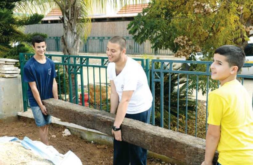 (From left to right) Sagi Farhi, Lidor Fachima and Iddo Ben-David help the Bayhesain family fix up their garden. (photo credit: KOBY KOENKAS)