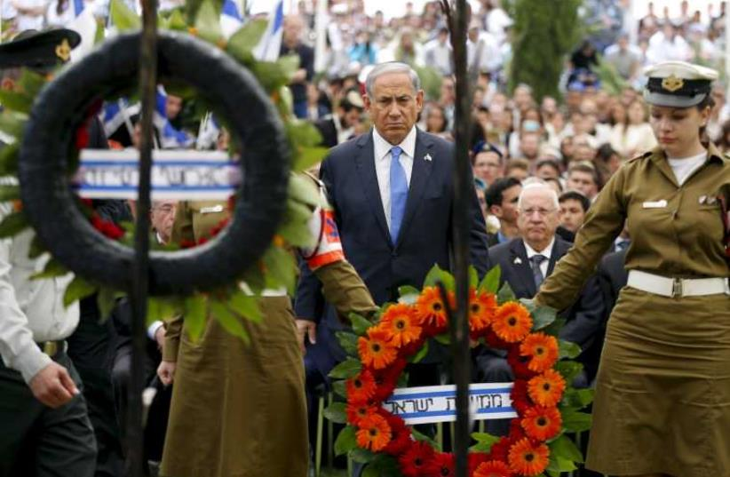 Netanyahu stands during a Remembrance Day ceremony at Mount Herzl military cemetery in Jerusalem April 22, 2015. (photo credit: REUTERS)