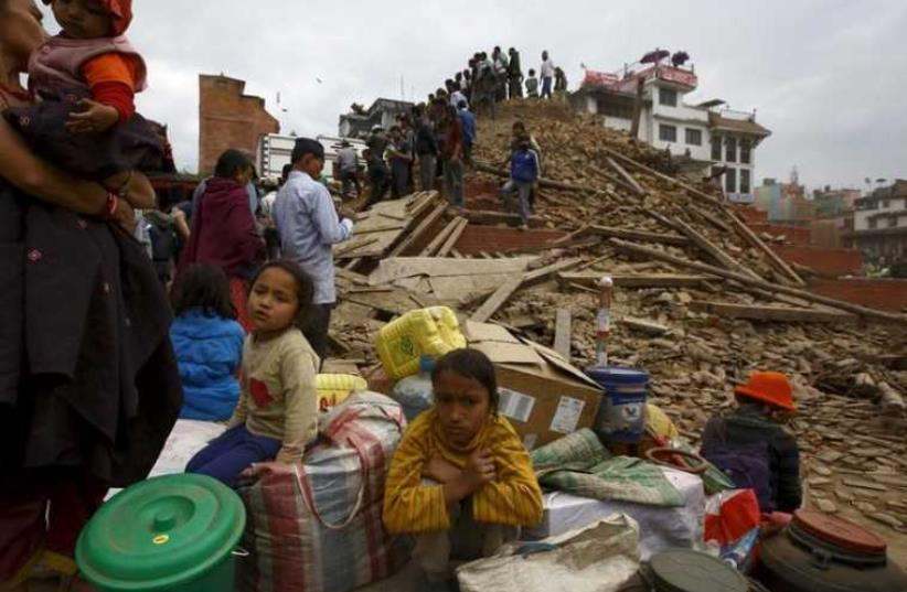 People sit with their belongings outside a damaged temple in Bashantapur Durbar Square after a major earthquake hit Kathmandu, Nepal April 25, 2015. (photo credit: REUTERS)