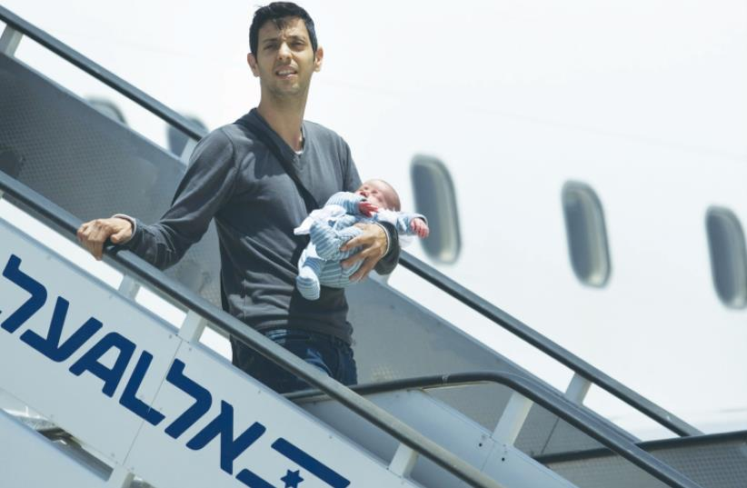 AN ISRAELI holds his surrogate-born baby as he disembarks yesterday from a plane at Ben-Gurion Airport after being evacuated from Nepal. (photo credit: AMIR COHEN - REUTERS)