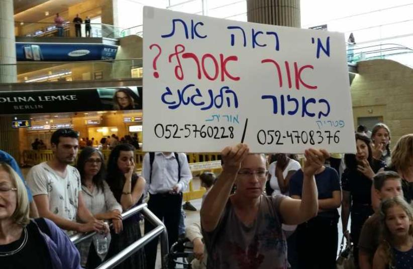 At Ben-Gurion Airport, Orit Asraf holds up a sign asking for information on her son who is missing in Nepal (photo credit: BEN HARTMAN)