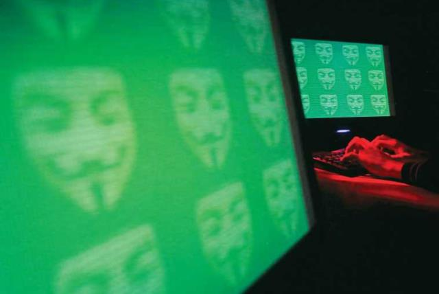 The logo for the cyber hacking group 'Anonymous' is seen on computer screens. (photo credit: REUTERS)
