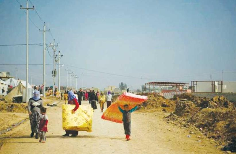 Refugees in Dohuk, Iraqi Kurdistan, carry mattresses provided by IsraAid. (photo credit: ISRAAID)
