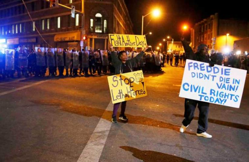 Protesters hold up signs in front of a line of police in Baltimore (photo credit: REUTERS)