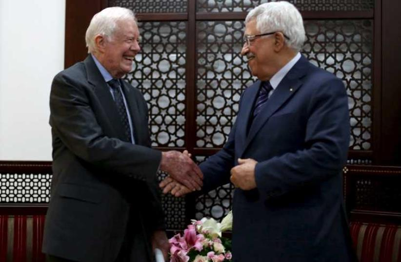 Palestinian President Mahmoud Abbas (R) shakes hands with former US president Jimmy Carter during their meeting in the West Bank city of Ramallah (photo credit: REUTERS)