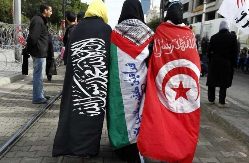 Girls walk the street dressed in (L-R) the Salafi, Palestinian and Tunisian flags during the second anniversary of the Tunisian Revolution in Tunis (photo credit: REUTERS)