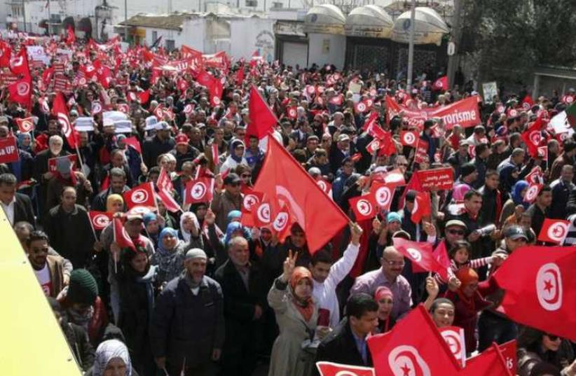 Tunisians wave their national flags. (photo credit: REUTERS)
