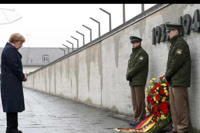 German Chancellor Merkel observes a moment of silence as she lays a wreath during a ceremony at the memorial in the former German Nazi concentration camp in Dachau. (photo credit: REUTERS)