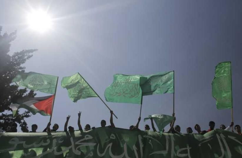 Palestinians wave Hamas and Palestinian flags (photo credit: REUTERS)