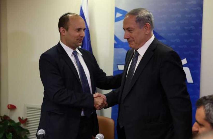 Prime Minister Benjamin Netanyahu (R) shakes hands with Bayit Yehudi chief Naftali Bennett (photo credit: TWITTER / TAL SCHNEIDER)