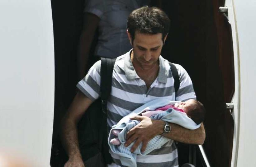 An Israeli man holds his baby, born to a surrogate mother, after being evacuated from Nepal and landing at Sde Dov Airport in Tel Aviv on April 27. (photo credit: NIR ELIAS / REUTERS)