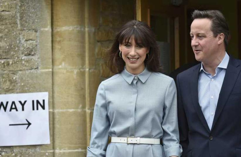 Britain's Prime Minister David Cameron and his wife Samantha leave after voting in Spelsbury, central England, May 7 (photo credit: REUTERS)