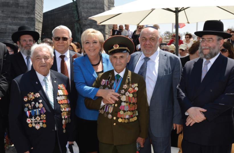 NETANYA MAYOR Miriam Feirberg Ikar stands with World War II Jewish veterans at a ceremony to mark 70 years since VE Day in the coastal city on Wednesday. (photo credit: RAN ELIYAHU)
