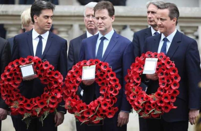 Ed Miliband (L) who resigned as leader of the Labour Party, Nick Clegg who resigned as leader of the Liberal Democrats, and Britain's Prime Minister David Cameron (R) carry wreaths of poppies as they pay tribute at the Cenotaph to mark the 70th anniversary of VE Day in London (photo credit: REUTERS)