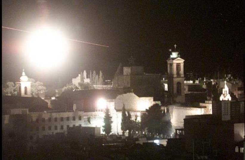 A flare and bullets fly over Bethlehem's center during an IDF attack on the Church of the Nativity, April 4, 2002 (photo credit: REUTERS)