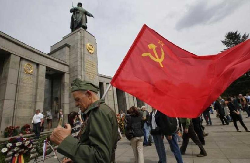 A man wearing a Red Army uniform holds a Soviet flag during celebrations to mark Victory Day